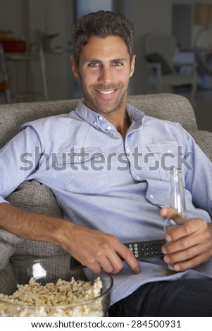 Hispanic Man On Sofa Watching TV