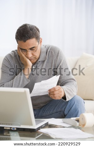 Hispanic man paying bills - stock photo