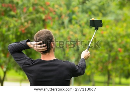 Hispanic man posing with selfie stick in park environment, his back facing camera. - stock photo