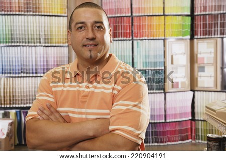 Hispanic man standing in front of paint swatches - stock photo