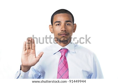 Hispanic man taking oath or pledge with right hand raised and serious expression - stock photo