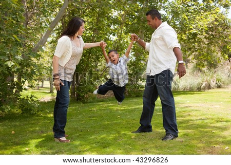 Hispanic Man, Woman and Child having fun in the park. - stock photo