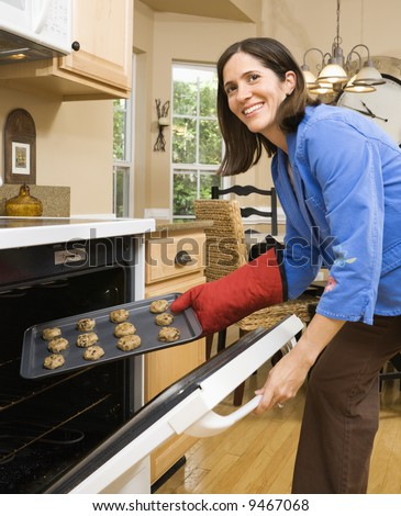 Hispanic mid adult woman putting cookies into oven and smiling at viewer.
