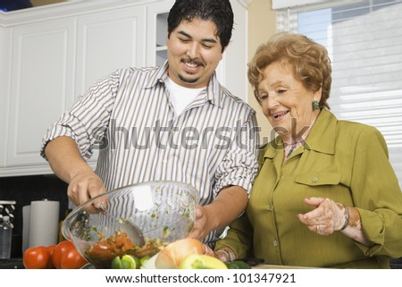 Hispanic mother and adult son preparing food in kitchen - stock photo