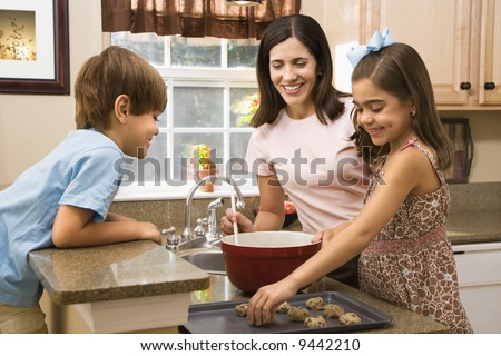 Hispanic mother and children in kitchen making cookies. - stock photo