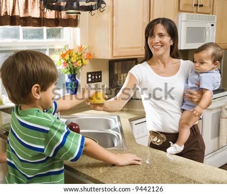 Hispanic mother and children in kitchen with juice. - stock photo