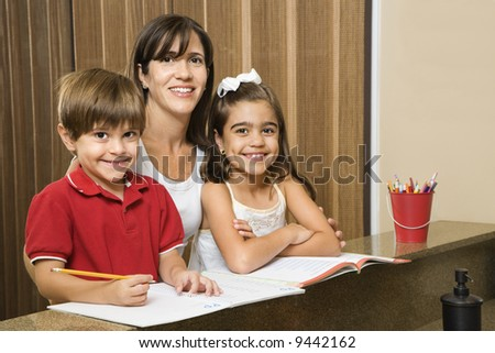 Hispanic mother and children smiling at viewer with homework. - stock photo