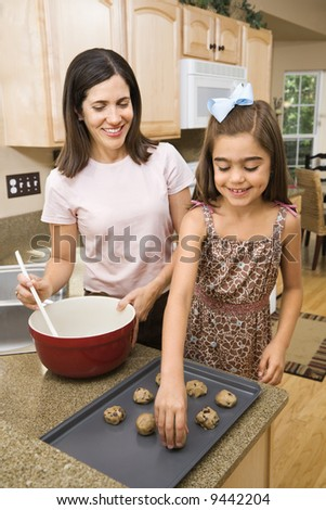 Hispanic mother and daughter in kitchen making cookies. - stock photo