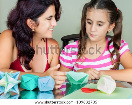 Hispanic mother and daughter making paper models (origami) at home - stock photo