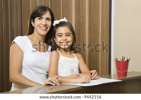 Hispanic mother and daughter portrait with homework. - stock photo