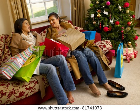 Hispanic mother and daughter resting after Christmas shopping - stock photo