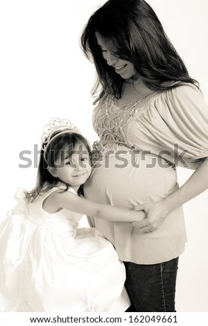 Hispanic mother and daughter waiting the arrival of a new baby sister