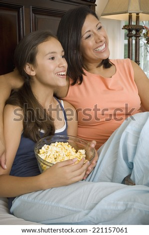 Hispanic mother and daughter watching television
