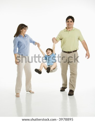 Hispanic mother and father swinging son against white background. - stock photo