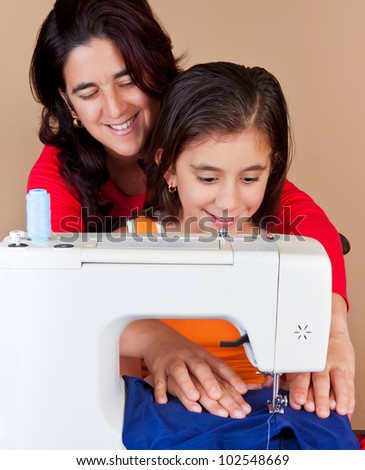 Hispanic mother  and her daughter using a sewing machine and sharing a good time together - stock photo