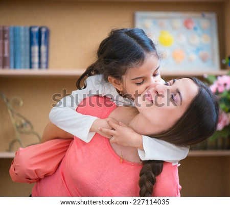 Hispanic mother and little daughter playing at home - stock photo