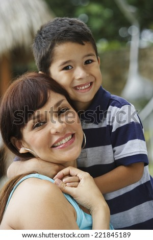 Hispanic mother and son hugging - stock photo