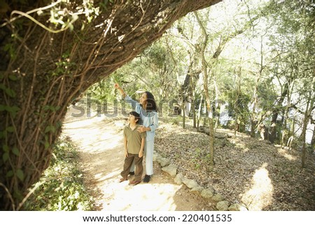Hispanic mother and son on nature trail - stock photo