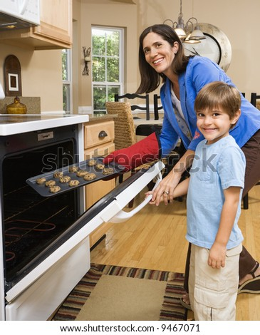 Hispanic mother and son putting cookies into oven and smiling at viewer. - stock photo