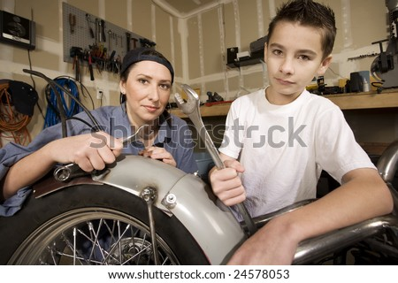 Hispanic mother and son working on motorcycle in garage - stock photo