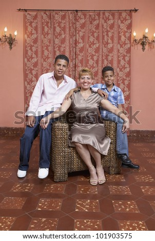 Hispanic mother and sons sitting on chair
