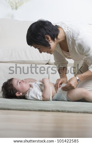 Hispanic mother changing baby's diaper