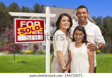 Hispanic Mother, Father and Daughter in Front of Their New Home with Sold Home For Sale Real Estate Sign. - stock photo