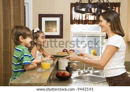 Hispanic mother handing healthy breakfast to young children in home kitchen. - stock photo