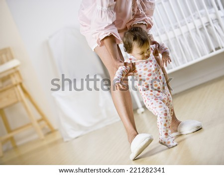 Hispanic mother helping baby walk - stock photo