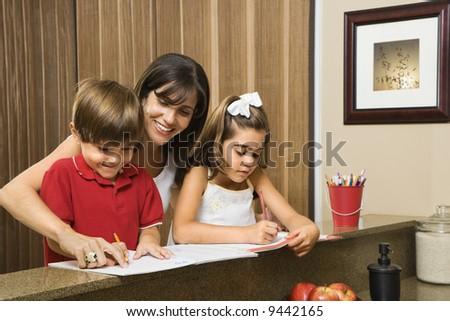 Hispanic mother helping children with homework. - stock photo