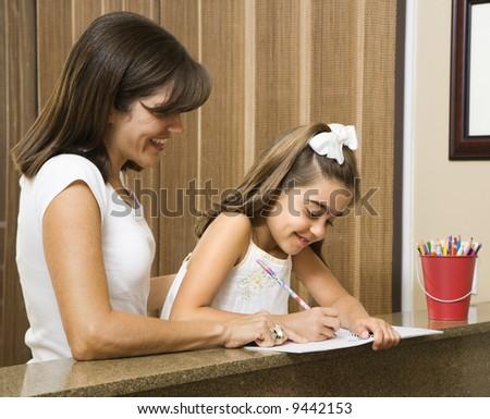 Hispanic mother helping daughter with homework. - stock photo