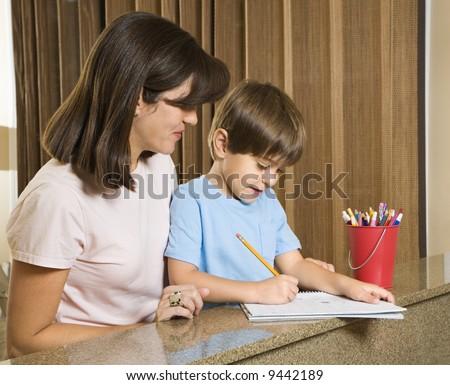 Hispanic mother helping son with homework. - stock photo