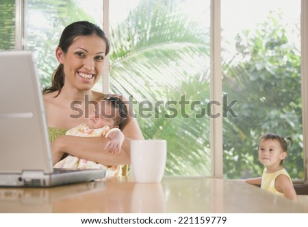 Hispanic mother holding baby - stock photo