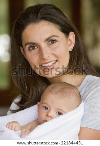 Hispanic mother holding baby in towel - stock photo