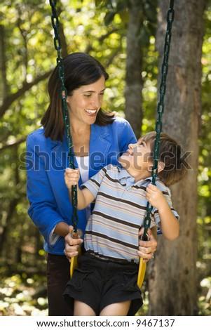 Hispanic mother pushing son on swing and making eye contact. - stock photo