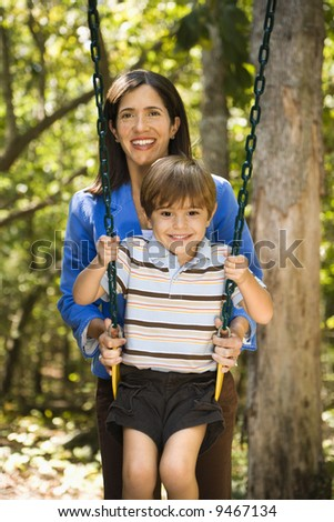 Hispanic mother pushing son on swing and smiling at viewer. - stock photo