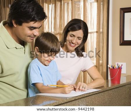 Hispanic parents helping son with homework. - stock photo