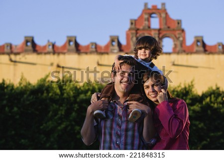 Hispanic parents holding son on shoulders - stock photo