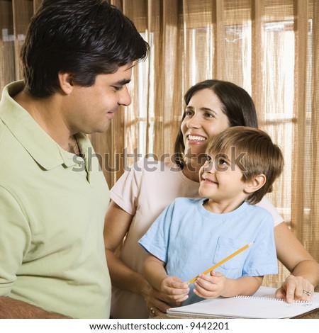 Hispanic parents making eye contact with son doing homework. - stock photo