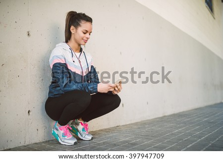Hispanic runner woman squatting and looking her smart phone
