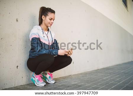 Hispanic runner woman squatting and looking her smart phone - stock photo