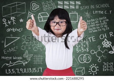 Hispanic schoolgirl wearing glasses and showing thumbs up in the class - stock photo