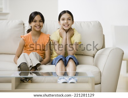Hispanic sisters sitting on sofa - stock photo