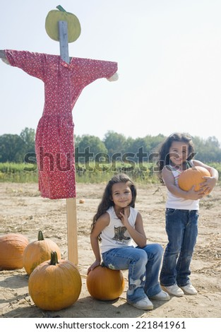 Hispanic sisters with pumpkins and scarecrow - stock photo