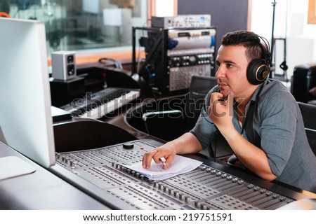Hispanic sound engineer working at mixing panel in the recording studio - stock photo
