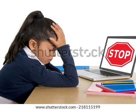 hispanic sweet little girl crying and suffering internet bullying and abuse at school sitting at desk with computer and stop sign  - stock photo