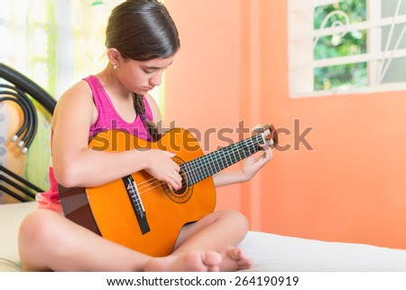 Hispanic teenage girl playing guitar in her bedroom - stock photo