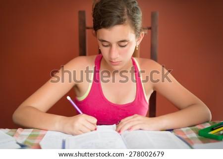 Hispanic teenage girl studying at home - stock photo