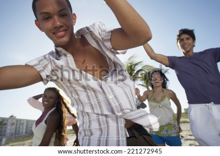 Hispanic teenaged boy with friends in background - stock photo