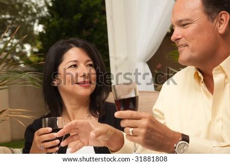 Hispanic Woman and Caucasian Man Enjoying Wine on the Patio. - stock photo